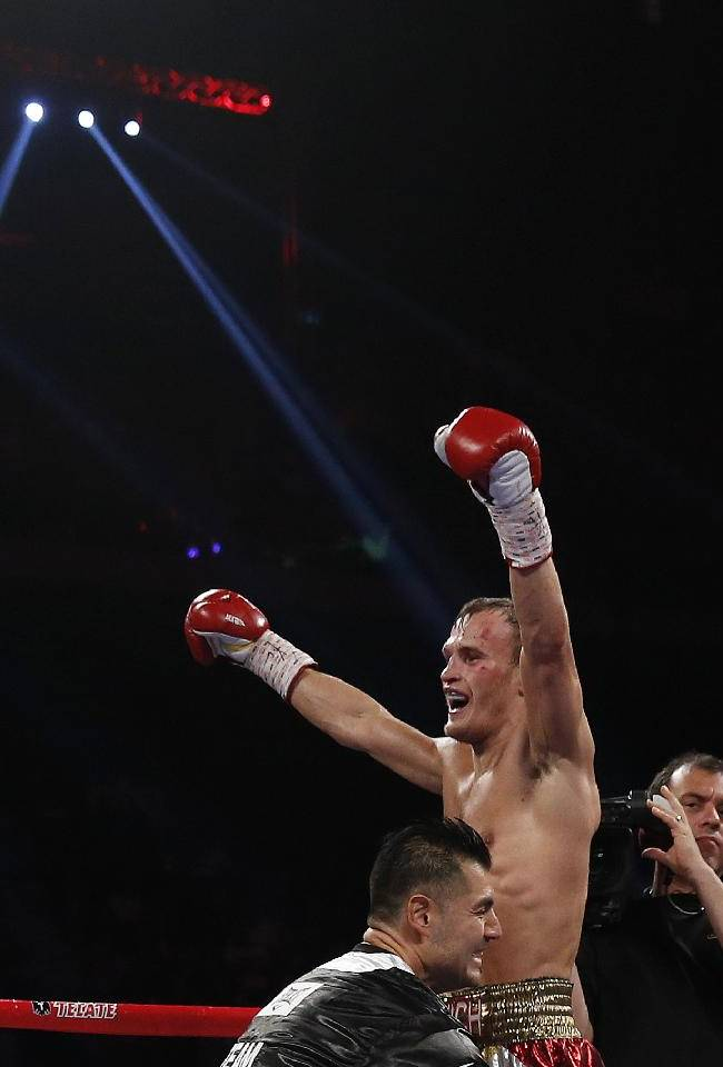 Russia's Evgeny Gradovich celebrates after defeating Australia's Billy Dib at their IBF featherweight title bout Sunday, Nov. 24, 2013, in Macau. Gradovich retained the title when Dib quit in the ninth round