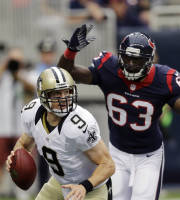 New Orleans Saints quarterback Drew Brees (9) scrambles to pass as Houston Texans linebacker Willie Jefferson (63) moves in during the first half of a preseason NFL football game on Sunday, Aug. 25, 2013, in Houston. (AP Photo/Eric Gay)