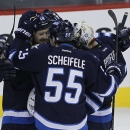 The Winnipeg Jets' Devin Setoguchi (40), Olli Jokinen (12), Mark Scheifele (55) and goaltender Ondrej Pavelec (31) celebrate a win over the Philadelphia Flyers after penalty shots in NHL hockey game action in Winnipeg, Manitoba, Friday, Nov. 15, 2013 The