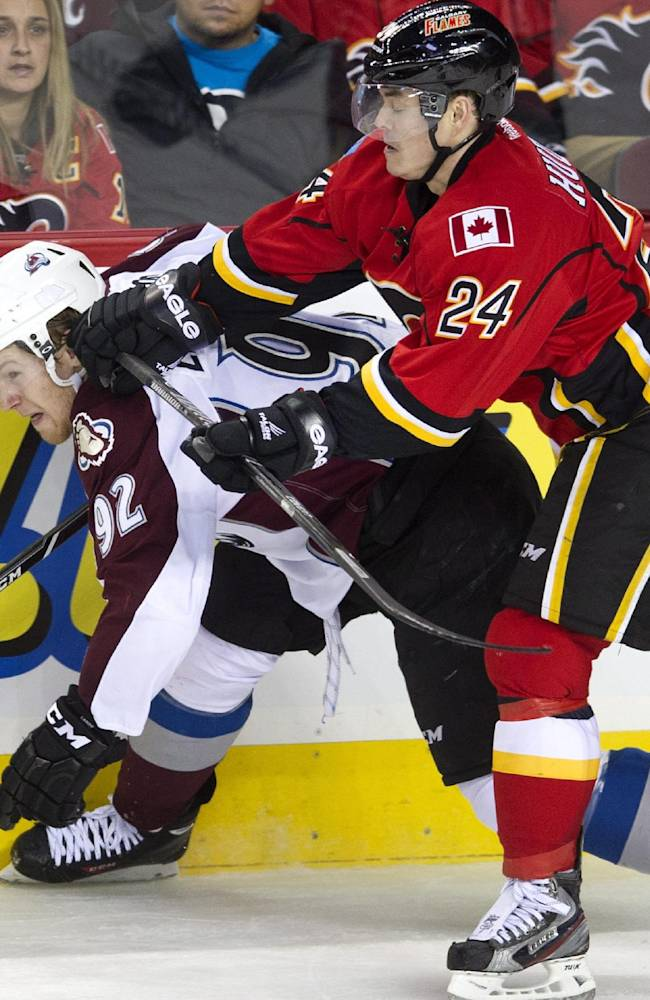 Colorado Avalanche's Gabriel Landeskog, left, from Sweden, takes a hit from Calgary Flames' Jiri Hudler, from Czech Republic, during the second period of an NHL hockey game, Friday, Dec. 6, 2013 in Calgary, Alberta