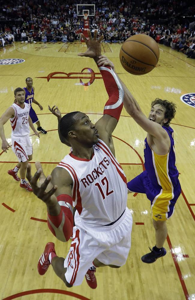 Houston Rockets' Dwight Howard (12) reaches for a rebound with Los Angeles Lakers' Pau Gasol, right, during the fourth quarter of an NBA basketball game Thursday, Nov. 7, 2013, in Houston. The lakers won 99-98