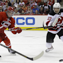 Carolina Hurricanes' Andrei Loktionov (8), of Russia, and New Jersey Devils' Peter Harrold (10) chase the puck during the second period of an NHL hockey game in Raleigh, N.C., Saturday, April 5, 2014 The Associated Press