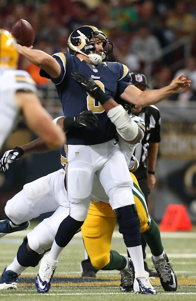 St. Louis Rams quarterback Sam Bradford is hit by Green Bay Packers linebacker/defensive end Julius Peppers in the second quarter during an NFL preseason football game, Saturday, Aug. 16, 2014, in St. Louis