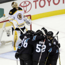 The San Jose Sharks celebrate a goal by Tommy Wingels in front of Boston Bruins goalie Tuukka Rask, top left, of Finland, during the second period of an NHL hockey game Thursday, Dec. 4, 2014, in San Jose, Calif The Associated Press