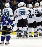 Tampa Bay Lightning right wing Martin St. Louis (26) skates off as members of the San Jose Sharks celebrate their 5-4 win during an NHL hockey game Saturday, Jan. 18, 2014, in Tampa, Fla. St. Louis scored all for goals for his team. (AP Photo/Chris O'Meara)