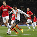 Donetsk's Douglas Costa, No 20, gets past Manchester United's Rio Ferdinand, left, to take a shot on goal during their Champions League group A soccer match between Manchester United and Shakhtar Donetsk at Old Trafford Stadium, Manchester, England, Tuesd