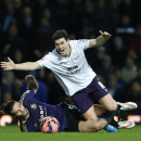 Everton's Gareth Barry, top, falls as he is tackled by West Ham United's Andy Carroll during their English FA Cup third round replay soccer match between West Ham United and Everton at the Boleyn Ground stadium in London, Tuesday, Jan. 13, 2015