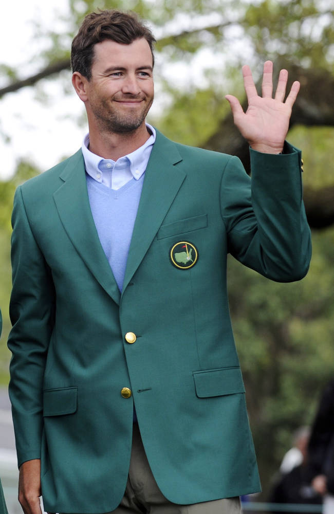 The 2013 Masters champion Adam Scott, of Australia, waves to a crowd during a trophy presentation for the