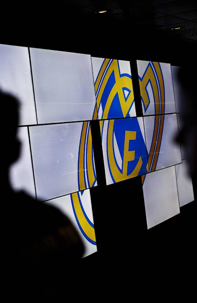 In this picture taken on May 18, 2014, Real Madrid's supporters are backlighted by screens displaying the Real Madrid team emblem on the trophies gallery of the Santiago Bernabeu stadium in Madrid, Spain. The European Union is investigating whether government loan guarantees for seven soccer clubs violate EU competition law, designed in part to prevent businesses from enjoying unfair advantage through state intervention. The probe is examining tax breaks granted to the Real Madrid, Barcelona, Athletic Bilbao and Osasuna soccer clubs _ but that's a small part of government assistance to Spain's soccer league, according to the AP review. (AP Photo/Daniel Ochoa de Olza)