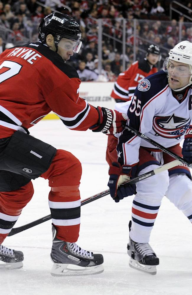 Columbus Blue Jackets' Mark Letestu, right, passes the puck by New Jersey Devils' Mark Fayne during the first period of an NHL hockey game on Thursday, Feb. 27, 2014, in Newark, N.J