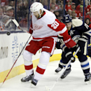 Detroit Red Wings' Drew Miller, left, works for the puck against Columbus Blue Jackets' James Wisniewski in the first period of an NHL hockey game in Columbus, Ohio, Tuesday, March 25, 2014 The Associated Press