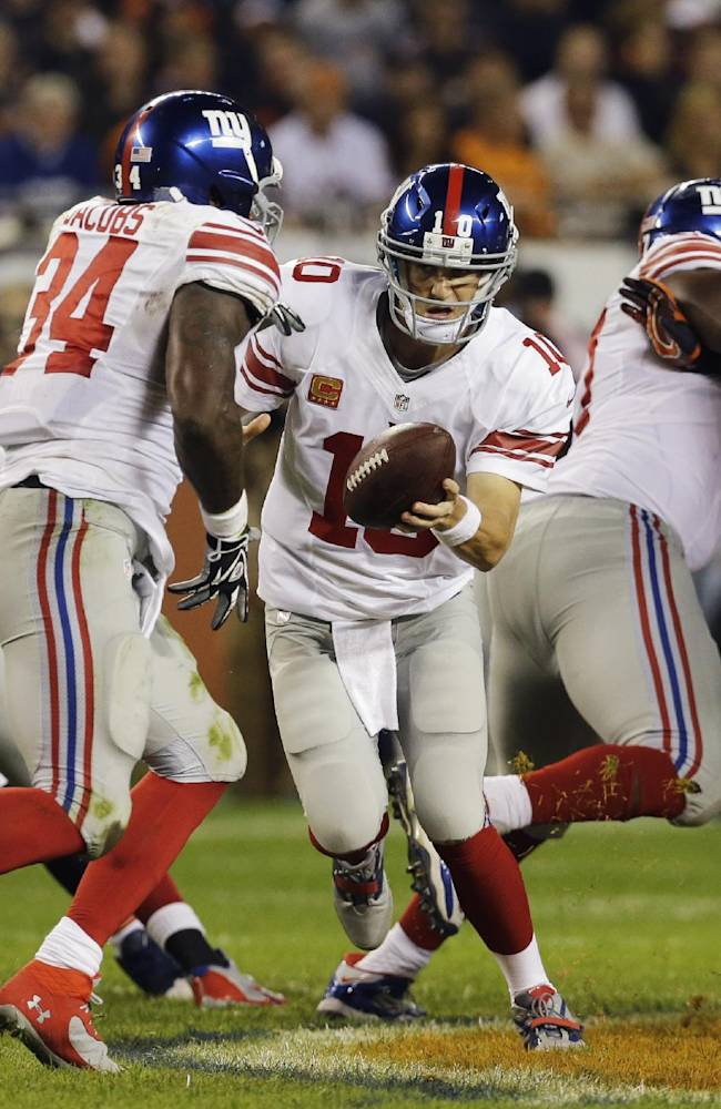 New York Giants quarterback Eli Manning (10) hands off to running back Brandon Jacobs (34) in the first half of an NFL football game against the Chicago Bears, Thursday, Oct. 10, 2013, in Chicago