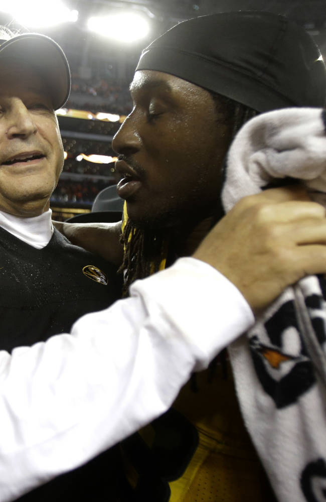 Missouri head coach Gary Pinkel and defensive lineman Markus Golden (33) embrace after beating Oklahoma State 41-31 at the Cotton Bowl NCAA college football game, Friday, Jan. 3, 2014, in Arlington, Texas. (AP Photo/Tim Sharp)