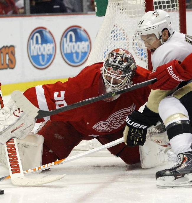 Detroit Red Wings goalie Jonas Gustavsson (50), of Sweden, tries to clear the puck away from Pittsburgh Penguins' Chris Kunitz (14) during the third period of an NHL hockey game on Saturday, Dec. 14, 2013, in Detroit. The Penguins defeated the Red Wings 4-1