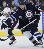 Winnipeg Jets' Blake Wheeler (26) attempts to get around Colorado Avalanche's Jan Hejda (8) as they drive for the puck during the second period of an NHL hockey game Wednesday, March 19, 2014, in Winnipeg, Manitoba. (AP Photo/The Canadian Press, John Woods)
