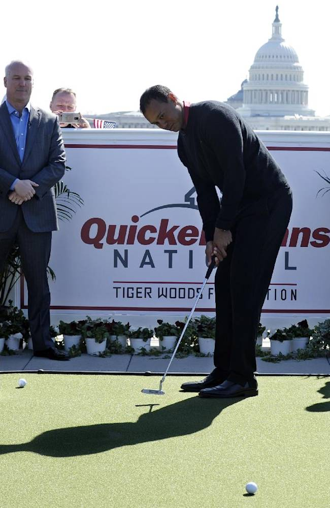 Tiger Woods, center, putts during a putting challenge at the Newseum in Washington, Monday, March 24, 2014. Woods and Quicken Loans Chief Executive Officer Bill Emerson, left, participated in the putting challenge to have the mortgage payments paid for three military families for one month. Earlier, Woods and Emerson announced that Quicken Loans had signed a multi-year agreement to become the title sponsor of the Quicken Loans National to be played at Congressional in Bethesda, Md., in June