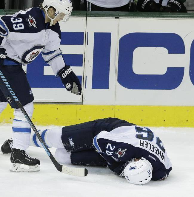 Winnipeg Jets defenseman Tobias Enstrom (39) skates over to check on teammate right wing Blake Wheeler (26) after Wheeler took a hard hit during the third period of an NHL hockey game Monday, March 24, 2014, in Dallas. The Stars won 2-1. Wheeler left the game with shoulder injury