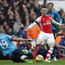 Arsenal's Laurent Koscielny, right, kicks the ball clear as Stoke City's Jonathan Walters slides in to tackle during their English Premier League soccer match between Arsenal and Stoke City at the Emirates stadium in London, Sunday, Jan. 11, 2015