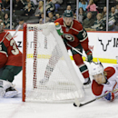 Montreal Canadiens right wing Dale Weise (22) falls as he brings the puck around the net in front of Minnesota Wild defenseman Jonas Brodin (25) as Wild goalie Darcy Kuemper, left, covers the net during the second period of an NHL hockey game in St. Paul