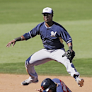 Milwaukee Brewers shortstop Jean Segura vaults over Cleveland Indians' Mike Aviles after throwing to first to complete a double play on Indians' Jeff Francoeur in the fifth inning of a spring training exhibition baseball game Sunday, March 9, 2014, in Goo