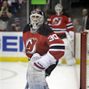As fellow goalie Cory Schneider, background, looks on, New Jersey Devils goalie Martin Brodeur warms up in the goal before an NHL hockey game against the Boston Bruins in Newark, N.J., Sunday, April 13, 2014 The Associated Press