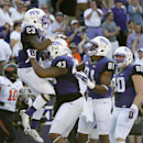 TCU running back B.J. Catalon (23) celebrates scoring a touchdown after a long run with Cliff Murphy (43), Ja'Juan Story (81) and Buck Jones (80) during the first half of an NCAA college football game against Oklahoma State, Saturday, Oct. 18, 2014, in Fort Worth, Texas. (AP Photo/Tony Gutierrez)