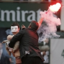 A security guard grabs a demonstrator as Spain's Rafael Nadal plays against compatriot David Ferrer in the final of the French Open tennis tournament, at Roland Garros stadium in Paris, Sunday June 9, 2013. (AP Photo/Michel Spingler)