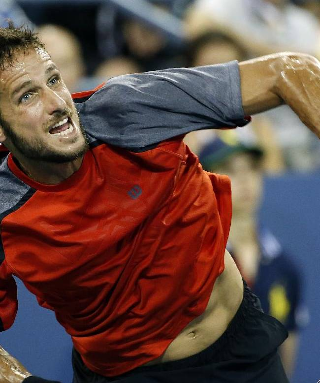 Feliciano Lopez, of Spain, serves to Dominic Thiem, of Austria, during the third round of the U.S. Open tennis tournament Sunday, Aug. 31, 2014, in New York