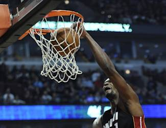 Miami Heat's Chris Bosh (1) dunks over Chicago Bulls Joakim Noah during the first quarter of an NBA basketball game in Chicago, Sunday, March 9, 2014. (AP Photo/ Paul Beaty)