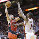 Toronto Raptors center Jonas Valanciunas (17) of Lithuania, goes up for a shot against Miami Heat center Chris Bosh (1) during the second half of an NBA basketball game, Monday, March 31, 2014 in Miami. Valanciunas had 14 points for the Raptors and Bosh