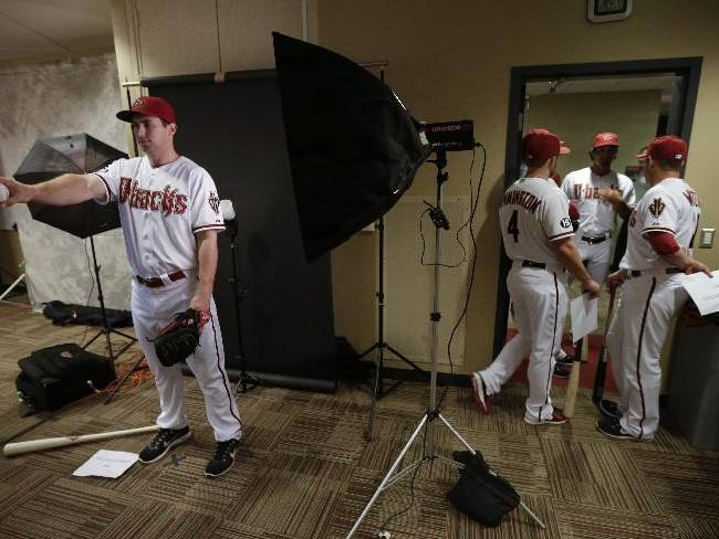 Arizona Diamondbacks first baseman Paul Goldschmidt, left, poses for a photograph as some of his teammate wait during the team's photo day before a spring training baseball workout, Wednesday, Feb. 19, 2014, in Scottsdale, Ariz