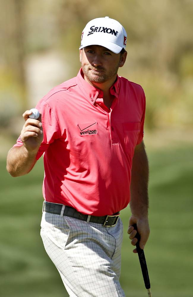 Graeme McDowell, of Northern Ireland, waves after a birdie on the seventh hole in his match against Hideki Matsuyama, of Japan, during the second round of the Match Play Championship golf tournament on Thursday, Feb. 20, 2014, in Marana, Ariz