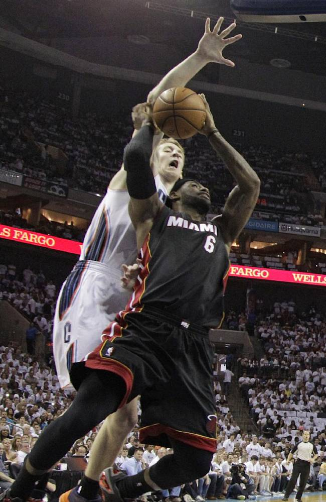Charlotte Bobcats' Cody Zeller, back, goes up to block the shot of Miami Heat's LeBron James, front, during the first half in Game 3 of an opening-round NBA basketball playoff series in Charlotte, N.C., Saturday, April 26, 2014