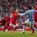 Manchester City's David Silva, second right, scores his second goal against Liverpool during their English Premier League soccer match at Anfield Stadium, Liverpool, England, Sunday April 13, 2014