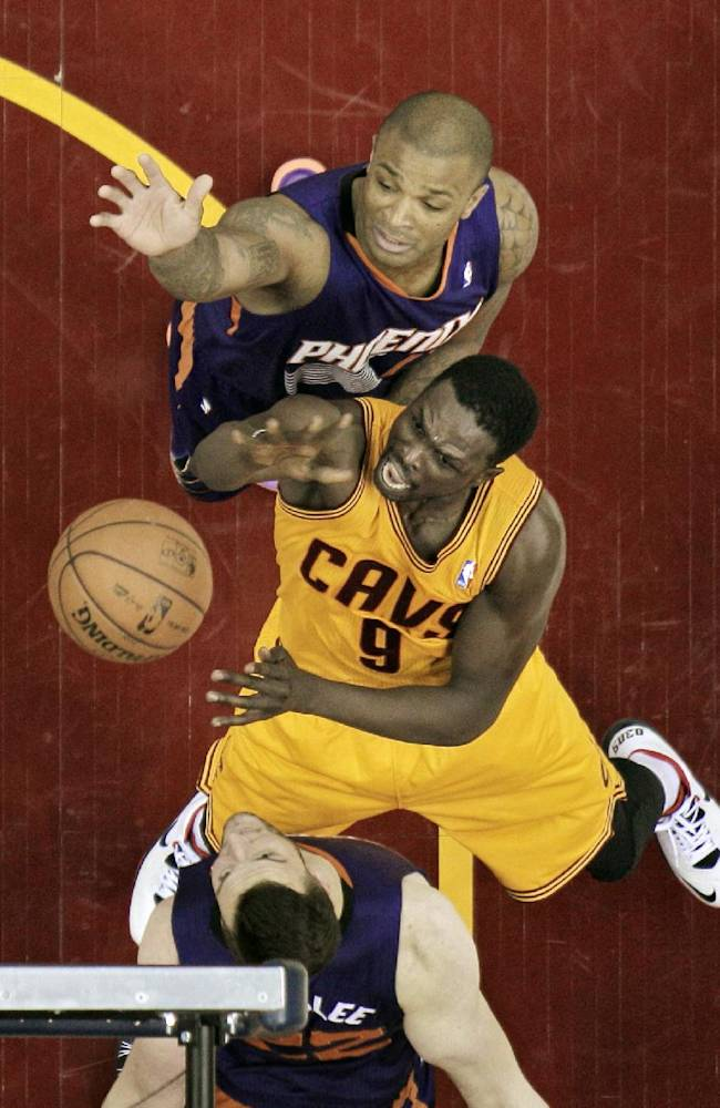 Cleveland Cavaliers' Luol Deng (9), from Sudan, puts up a shot against Phoenix Suns' P.J. Tucker, top and Miles Plumlee (22) in the first half of an NBA basketball game, Sunday, Jan. 26, 2014, in Cleveland