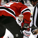 Chicago Blackhawks center Jonathan Toews, center, keeps his eye on the puck before it's dropped against New Jersey Devils center Adam Henrique, left, during the first period of an NHL hockey game, Tuesday, Dec. 9, 2014, in Newark, N.J The Associated Press