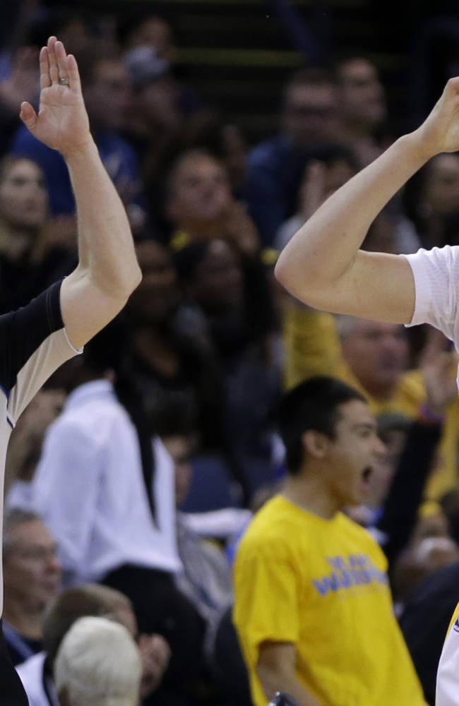 Golden State Warriors' Klay Thompson, right, gestures after scoring against the Sacramento Kings' during the second half of an NBA basketball game on Saturday, Nov. 2, 2013, in Oakland, Calif