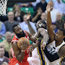 Houston Rockets' James Harden, left, pulls down a rebound as Utah Jazz's Marvin Williams, center, and teammate Derrick Favors, right, defend in the first quarter of an NBA basketball game Monday, Dec. 2, 2013, in Salt Lake City The Associated Press