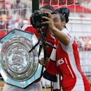 Arsenal's Santi Cazorla, right, takes a selfie with Alex Oxlade-Chamberlain as they celebrate their win against Manchester City with the trophy at the end of their English Community Shield soccer match at Wembley Stadium in London, Sunday, Aug. 10, 2014