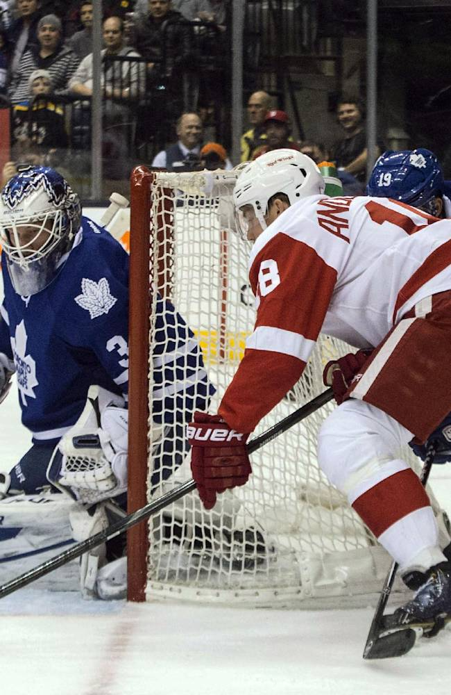 Detroit Red Wings' Joakim Andersson, centre right, scores on Toronto Maple Leafs goaltender James Reimer during first period NHL hockey action in Toronto on Saturday, Dec 21, 2013
