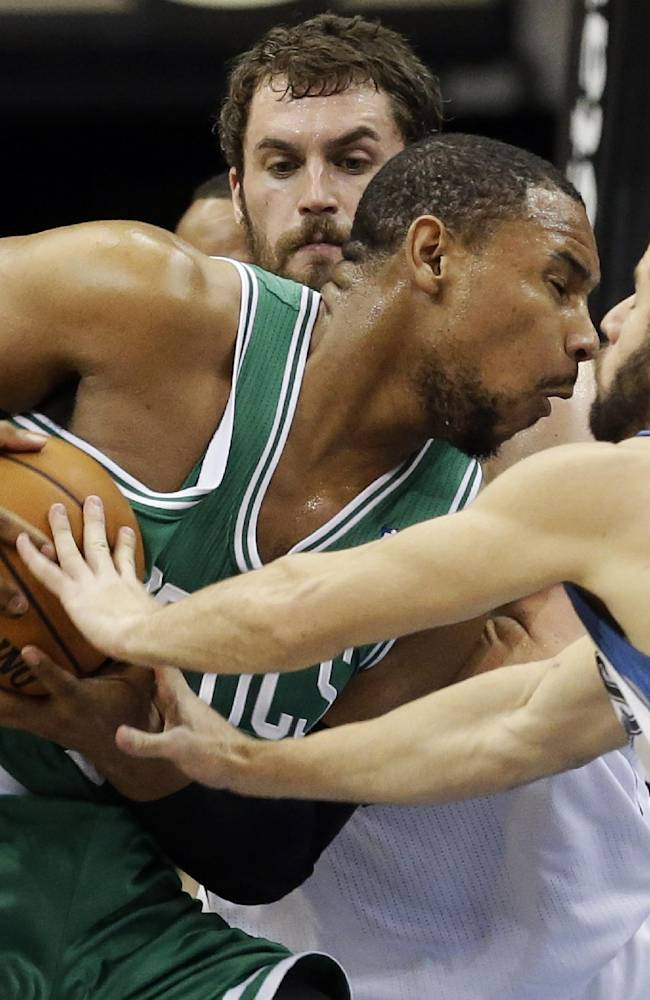 Boston Celtics' Jared Sullinger, left, attempts to drive between Minnesota Timberwolves' J.J. Barea, right, and Kevin Love in the first quarter of an NBA basketball game on Saturday, Nov. 16, 2013, Minneapolis