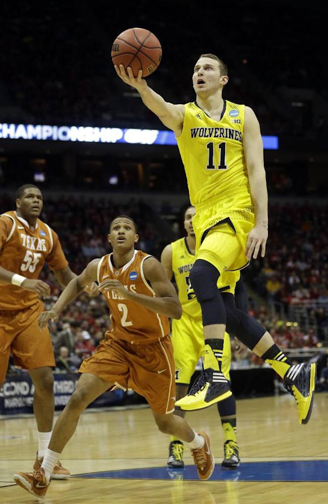 In this March 22, 2014 file photo, Michigan guard Nik Stauskas (11) drives to the basket during the first half of a game against Texas in Milwaukee. Sophomores Glen Robinson III and Stauskas helped the Wolverines win the Big Ten title and reach an  NCAA tournament regional final last season