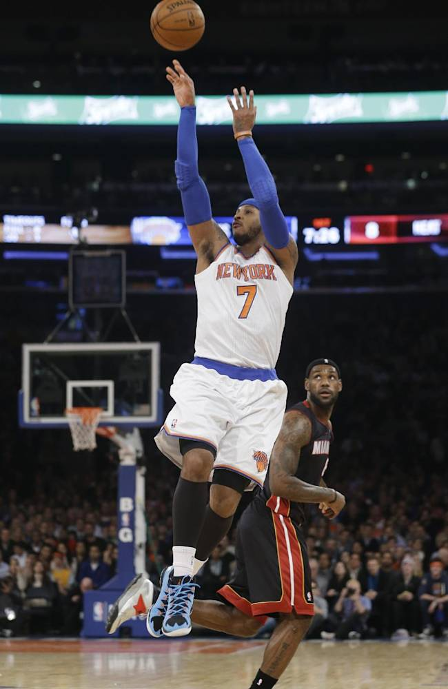 New York Knicks' Carmelo Anthony (7) gets past Miami Heat's LeBron James to shoot during the first half of an NBA basketball game on Thursday, Jan. 9, 2014, in New York