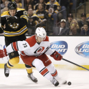 Carolina Hurricanes' Brett Bellemore (73) tries to hold back Boston Bruins' Milan Lucic during the second period of a NHL hockey game in Boston Saturday, Nov. 23, 2013 The Associated Press