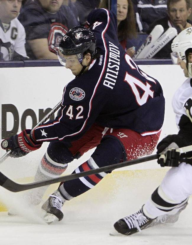 Columbus Blue Jackets' Artem Anisimov, left, of Russia, tries to clear the puck as Pittsburgh Penguins' Kris Letang defends during the second period of a first-round NHL playoff hockey game Monday, April 21, 2014, in Columbus, Ohio