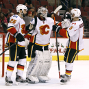 Calgary Flames goaltender Karri Ramo, center, of Finland, is congratulated by teammates Brandon Bollig (25) and Mark Giordano following the Flames' 3-0 shutout victory over the Arizona Coyotes in an NHL game Saturday, Nov. 29, 2014, in Glendale, Ariz The