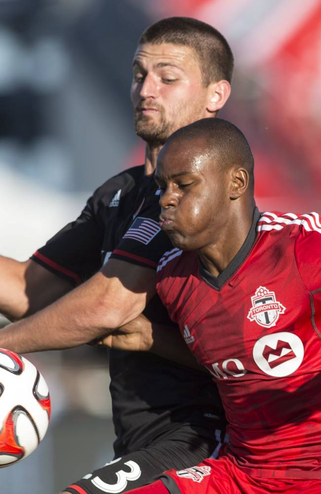 Toronto FC 's Jackson Goncalves, right, battles for the ball with D.C. United's Perry Kitchen during the first half of an MLS soccer game in Toronto on Saturday, July 5, 2014