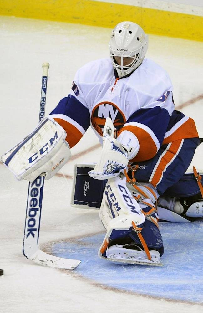New York Islanders goaltender Kevin Poulin makes a save during the third period of a preseason NHL hockey game against the New Jersey Devils, Thursday, Sept. 19, 2013, in Newark, N.J. The Islanders defeated the Devils 5-3