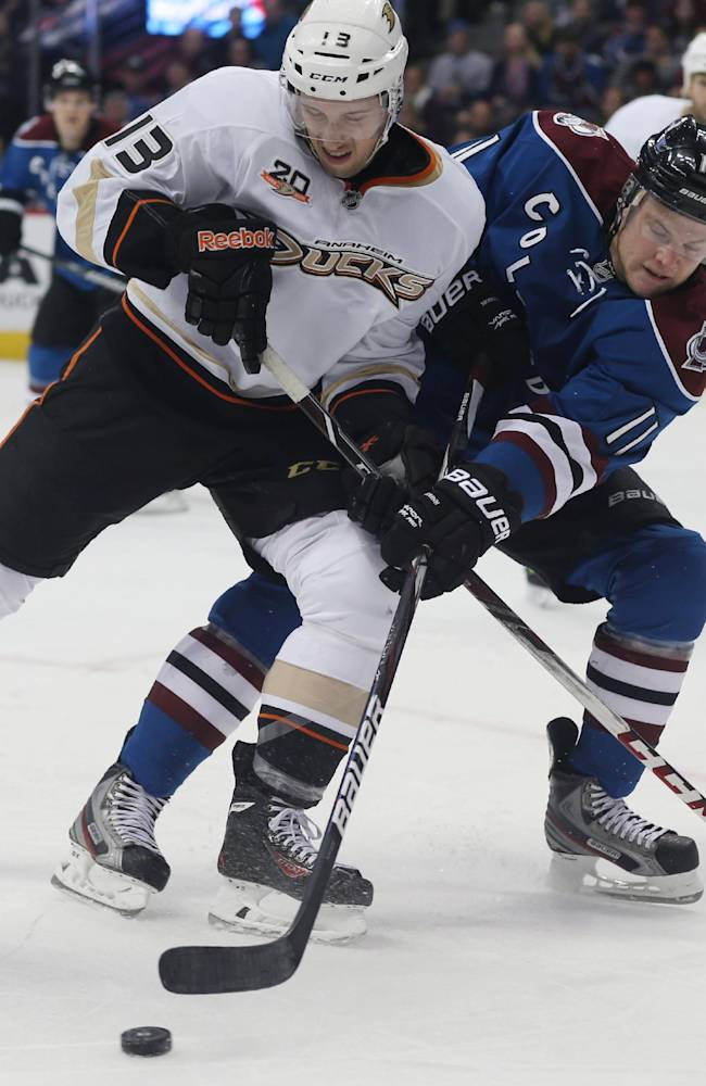 Anaheim Ducks center Nick Bonino, left, battles for control of puck with Colorado Avalanche left wing Jamie McGinn in the second period of an NHL hockey game in Denver on Friday, March 14, 2014
