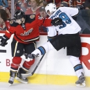 San Jose Sharks' Logan Couture, right, collides with Calgary Flames' Matt Stajan during the third period of an NHL hockey game in Calgary, Alberta, Saturday, Dec. 6, 2014 The Associated Press